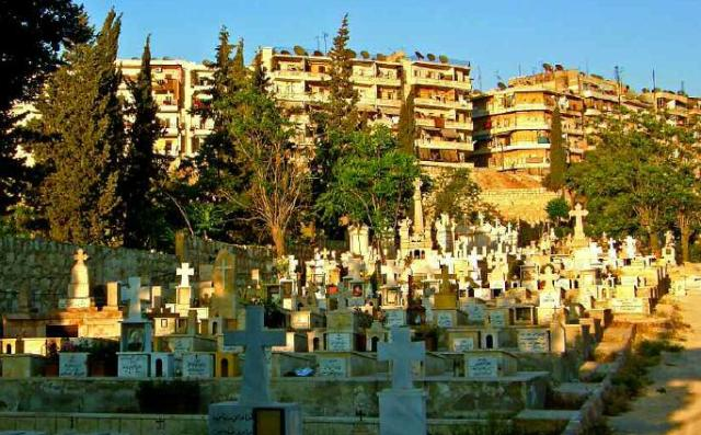 Los cementerios cristianos y al fondo bloques residenciales del barrio Cheik Maqsud en Alepo / Foto: Karlos Zurutuza