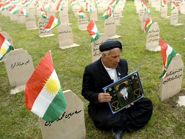 Un padre porta una foto de su hijo en el Cementerio de Halabca