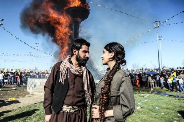 Una pareja de kurdos se miran de forma romántica enfrente del fuego de Newroz, en las celebraciones del nuevo año kurdo, en Diyarbakir (sudeste de Turquía), el viernes 21 de marzo de 2014 / Foto: Gurcan Ozturk